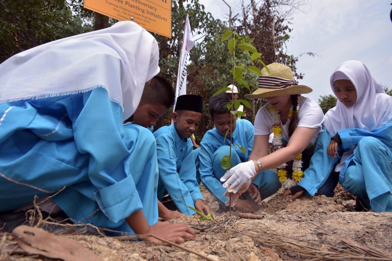 一緒に植樹をするボランティアと地元住民